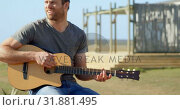 Купить «Front view of mid-adult caucasian man playing guitar on a sunny day 4k», видеоролик № 31881495, снято 22 июня 2018 г. (c) Wavebreak Media / Фотобанк Лори