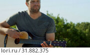 Купить «Front view of mid-adult caucasian man playing guitar on a sunny day 4k», видеоролик № 31882375, снято 22 июня 2018 г. (c) Wavebreak Media / Фотобанк Лори
