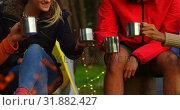 Купить «Friends toasting coffee mugs near campfire in the forest 4k», видеоролик № 31882427, снято 12 октября 2018 г. (c) Wavebreak Media / Фотобанк Лори