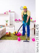 Купить «Young male contractor doing housework after party», фото № 31882475, снято 14 марта 2019 г. (c) Elnur / Фотобанк Лори