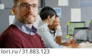 Купить «Male executive looking at camera in office 4k», видеоролик № 31883123, снято 16 июня 2018 г. (c) Wavebreak Media / Фотобанк Лори