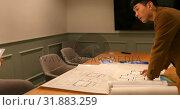 Купить «Side view of young Asian business people discussing over digital tablet in the conference room 4k», видеоролик № 31883259, снято 3 октября 2018 г. (c) Wavebreak Media / Фотобанк Лори