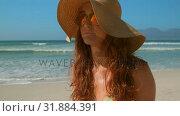 Купить «Beautiful young Caucasian woman in bikini with sunglasses and hat standing on beach 4k», видеоролик № 31884391, снято 14 ноября 2018 г. (c) Wavebreak Media / Фотобанк Лори