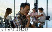 Купить «Thoughtful young Asian male executive sitting at table in conference room in office 4k», видеоролик № 31884399, снято 18 ноября 2018 г. (c) Wavebreak Media / Фотобанк Лори