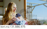 Купить «Front view of mid adult caucasian mother feeding milk her baby from bottle in a comfortable home 4k», видеоролик № 31886975, снято 22 июня 2018 г. (c) Wavebreak Media / Фотобанк Лори