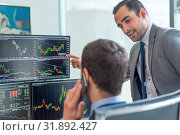 Купить «Businessmen trading stocks online. Stock brokers looking at graphs, indexes and numbers on multiple computer screens. Colleagues in discussion in traders office. Business success concept.», фото № 31892427, снято 9 июля 2020 г. (c) easy Fotostock / Фотобанк Лори