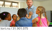 Купить «Caucasian male teacher teaching his kids about globe in classroom 4k», видеоролик № 31901075, снято 10 ноября 2018 г. (c) Wavebreak Media / Фотобанк Лори