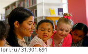 Купить «Asian female teacher teaching schoolkids in school library 4k», видеоролик № 31901691, снято 10 ноября 2018 г. (c) Wavebreak Media / Фотобанк Лори