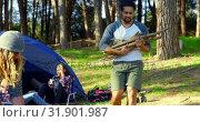Купить «Man carrying wooden stick near camp in forest 4k», видеоролик № 31901987, снято 12 октября 2018 г. (c) Wavebreak Media / Фотобанк Лори