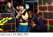 Купить «Multiracial couple playing lasertag», фото № 31902751, снято 23 января 2019 г. (c) Яков Филимонов / Фотобанк Лори