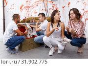 Купить «Young people in lost room with bloody walls», фото № 31902775, снято 8 октября 2018 г. (c) Яков Филимонов / Фотобанк Лори