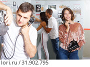 Купить «Girl and guy checking telephone set in escape room», фото № 31902795, снято 8 октября 2018 г. (c) Яков Филимонов / Фотобанк Лори