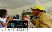 Купить «Young Caucasian male firefighter teaching schoolgirl about fire safety in classroom 4k», видеоролик № 31902843, снято 10 ноября 2018 г. (c) Wavebreak Media / Фотобанк Лори
