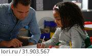 Купить «Front view of Caucasian male teacher teaching schoolgirl in the classroom 4k», видеоролик № 31903567, снято 17 ноября 2018 г. (c) Wavebreak Media / Фотобанк Лори