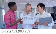 Купить «Multi-ethnic businessmen discussing over document in modern office 4k», видеоролик № 31903759, снято 18 ноября 2018 г. (c) Wavebreak Media / Фотобанк Лори