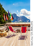 beautiful view to place of rest with sunbeds near funicular Col Raiser, captured with one of the dolomites famous mountains, the Sassolungo or Longkofel, in the background, on sunny summer clear day. Стоковое фото, фотограф Алексей Ширманов / Фотобанк Лори