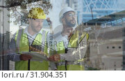 Male construction workers holding blueprints . Стоковое видео, агентство Wavebreak Media / Фотобанк Лори