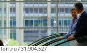 Купить «Business people moving down on escalator in the office 4k», видеоролик № 31904527, снято 21 ноября 2018 г. (c) Wavebreak Media / Фотобанк Лори