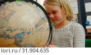 Купить «Front view of Caucasian schoolgirl studying globe at desk in classroom at school 4k», видеоролик № 31904635, снято 17 ноября 2018 г. (c) Wavebreak Media / Фотобанк Лори