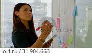 Купить «Side view of young Caucasian female executive with digital tablet working on glass board 4k», видеоролик № 31904663, снято 29 ноября 2018 г. (c) Wavebreak Media / Фотобанк Лори