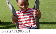Купить «Front view of African American schoolboy playing on a swing in school playground 4k», видеоролик № 31905051, снято 17 ноября 2018 г. (c) Wavebreak Media / Фотобанк Лори