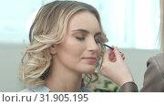 Professional make-up artist combing eyelashes of model in white room. Стоковое видео, видеограф Vasily Alexandrovich Gronskiy / Фотобанк Лори
