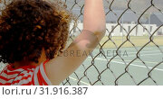 Купить «Rear view of mixed-race schoolgirl standing near wire mesh fence at school 4k», видеоролик № 31916387, снято 17 ноября 2018 г. (c) Wavebreak Media / Фотобанк Лори