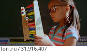 Side view of African American schoolgirl with spectacle learning math with abacus in classroom 4k. Стоковое видео, агентство Wavebreak Media / Фотобанк Лори