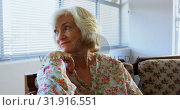 Front view of active Caucasian senior woman relaxing at nursing home 4k. Стоковое видео, агентство Wavebreak Media / Фотобанк Лори