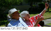 Купить «Front view of active Caucasian senior couple taking selfie with mobile phone in the garden of nursin», видеоролик № 31917843, снято 22 ноября 2018 г. (c) Wavebreak Media / Фотобанк Лори
