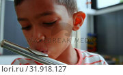 Купить «Front view of attentive Asian schoolboy playing flute in classroom at school 4k», видеоролик № 31918127, снято 17 ноября 2018 г. (c) Wavebreak Media / Фотобанк Лори