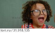Купить «Front view of mixed-race schoolgirl with spectacle shouting in classroom at school 4k», видеоролик № 31918135, снято 17 ноября 2018 г. (c) Wavebreak Media / Фотобанк Лори