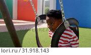 Купить «Side view of African American schoolboy playing on a swing in school playground 4k», видеоролик № 31918143, снято 17 ноября 2018 г. (c) Wavebreak Media / Фотобанк Лори