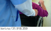 Close-up of Caucasian female doctor pushing senior patient in wheelchair at nursing home 4k. Стоковое видео, агентство Wavebreak Media / Фотобанк Лори