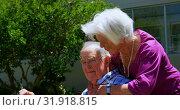 Купить «Side view of active Caucasian senior couple embracing each other in the garden of nursing home 4k», видеоролик № 31918815, снято 22 ноября 2018 г. (c) Wavebreak Media / Фотобанк Лори