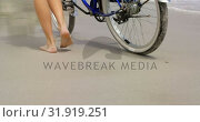 Low section of woman walking with a bicycle on the beach 4k. Стоковое видео, агентство Wavebreak Media / Фотобанк Лори