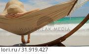 Купить «Rear view of Caucasian woman relaxing in a hammock at beach 4k», видеоролик № 31919427, снято 12 ноября 2018 г. (c) Wavebreak Media / Фотобанк Лори
