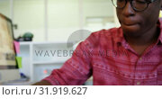 Купить «Front view of African American male graphic designer working at desk in office 4k», видеоролик № 31919627, снято 18 ноября 2018 г. (c) Wavebreak Media / Фотобанк Лори