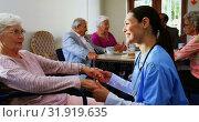 Side view of Caucasian female doctor consoling sad disabled senior woman at nursing home 4k. Стоковое видео, агентство Wavebreak Media / Фотобанк Лори