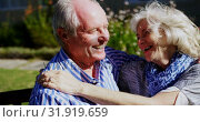 Front view of active Caucasian senior couple embracing each other in the garden of nursing home 4k. Стоковое видео, агентство Wavebreak Media / Фотобанк Лори