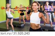 Купить «Portrait of sporty women exercising with barbell in fitness club», фото № 31920243, снято 26 июля 2017 г. (c) Яков Филимонов / Фотобанк Лори