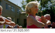 Side view of active mixed-race senior people performing yoga in the garden of nursing home 4k. Стоковое видео, агентство Wavebreak Media / Фотобанк Лори