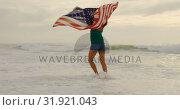 Купить «Front view of African American woman with waving American flag dancing on the beach 4k», видеоролик № 31921043, снято 12 ноября 2018 г. (c) Wavebreak Media / Фотобанк Лори