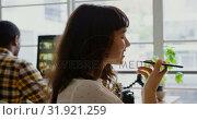 Купить «Female graphic designer talking on mobile phone in a modern office.», видеоролик № 31921259, снято 6 декабря 2018 г. (c) Wavebreak Media / Фотобанк Лори