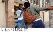 Купить «Woman clicking photo of her twin sister on a sidewalk in the city 4k», видеоролик № 31922171, снято 6 мая 2018 г. (c) Wavebreak Media / Фотобанк Лори