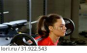 Купить «Woman exercising with barbell in a fitness studio 4k», видеоролик № 31922543, снято 26 июня 2018 г. (c) Wavebreak Media / Фотобанк Лори