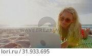 Купить «Woman in bikini and sunglasses using laptop on beach 4k», видеоролик № 31933695, снято 12 декабря 2018 г. (c) Wavebreak Media / Фотобанк Лори