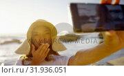 Купить «Woman taking selfie with mobile phone on the beach 4k», видеоролик № 31936051, снято 24 января 2019 г. (c) Wavebreak Media / Фотобанк Лори