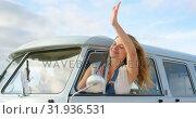 Купить «Woman waving out of camper van window 4k», видеоролик № 31936531, снято 9 января 2019 г. (c) Wavebreak Media / Фотобанк Лори