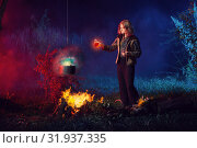 Купить «young witch by fire in night forest prepares magic potion», фото № 31937335, снято 31 июля 2019 г. (c) Майя Крученкова / Фотобанк Лори